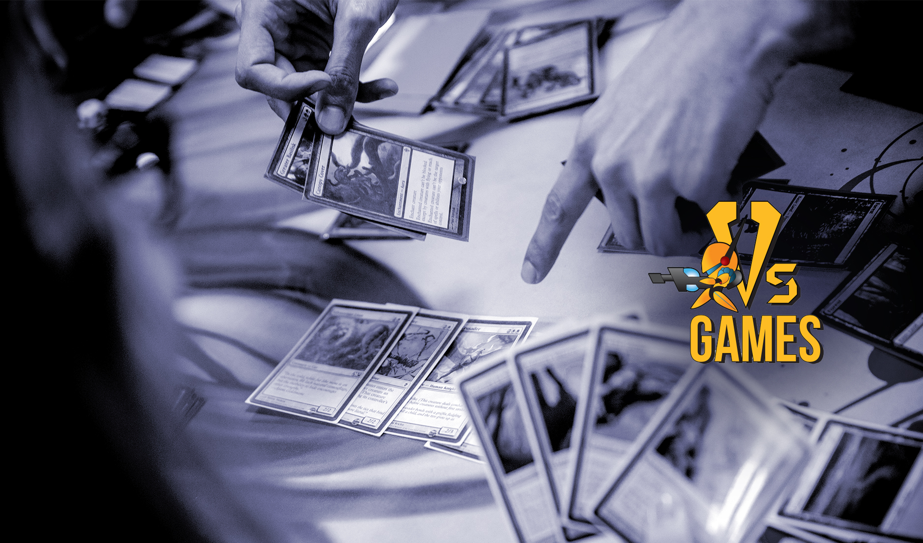 Header image, Vs games logo over a closeup of Magic cards being played