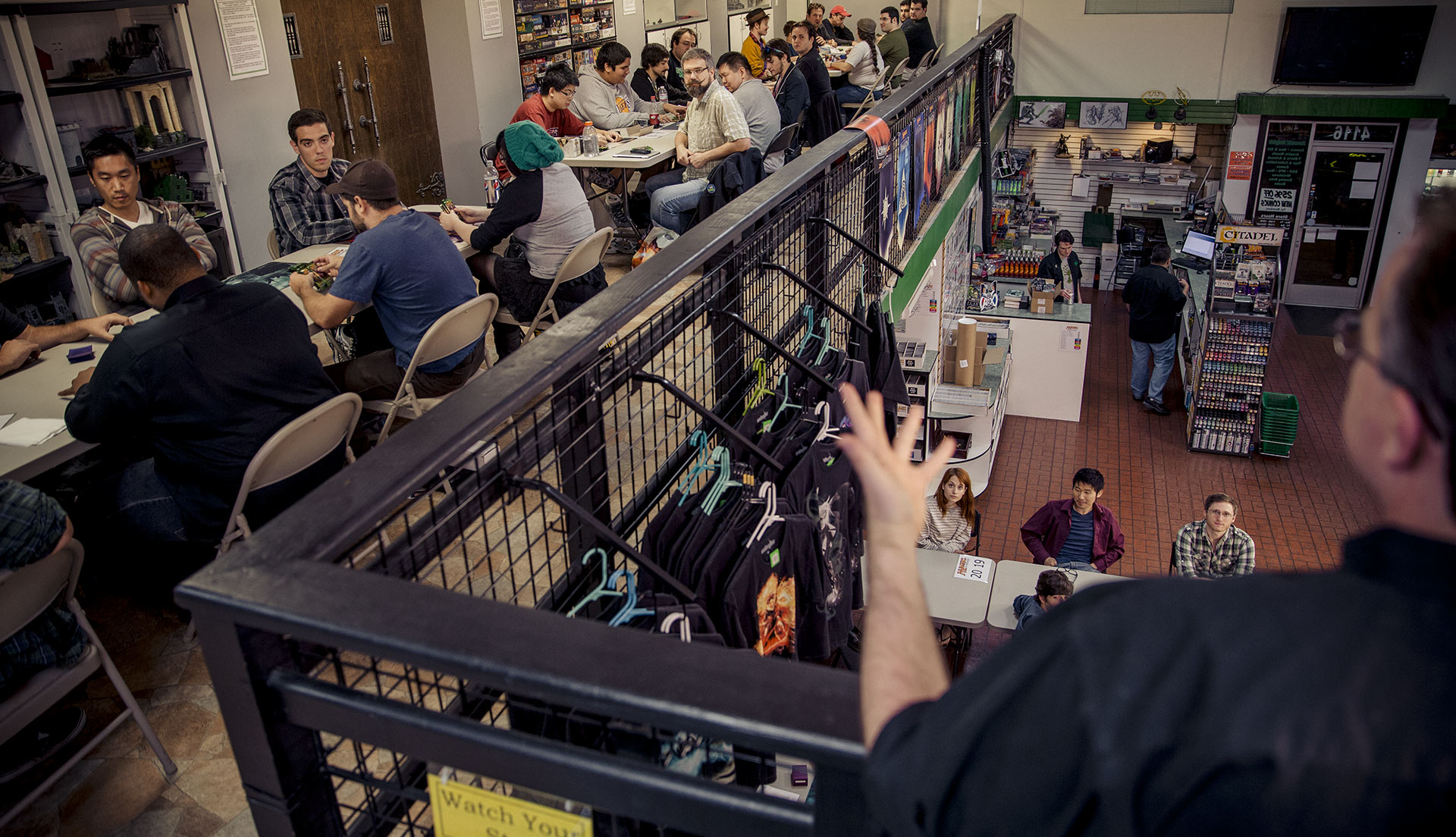 Header image, multiple tables with people playing Magic in a game store